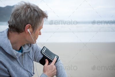 Man listening music on mobile phone at beach