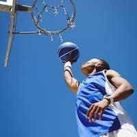 Low angle view of teenager playing basketball
