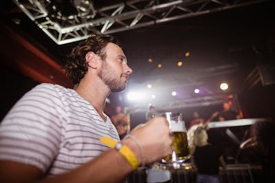 Low angle view of thoughtful man holding beer mug
