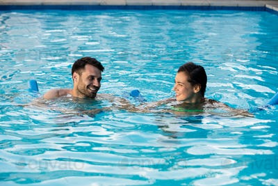 Young couple swimming with inflatable tubes