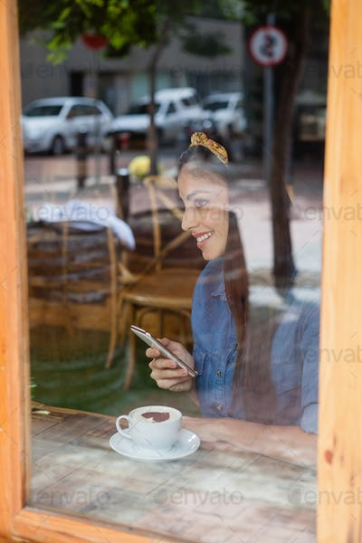 Smiling woman holding mobile phone while sitting at cafe