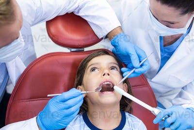 Dentists examining young patient in dental clinic