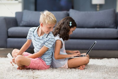 Boy looking behind while his sister using laptop in living room
