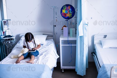 Patient using digital tablet on bed