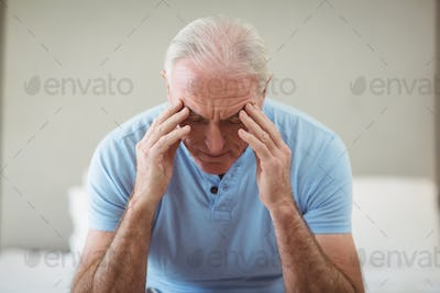 Stressed senior man sitting on bed