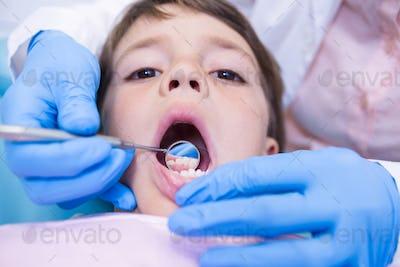 Dentist examining cute boy at clinic