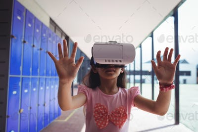 Schoolgirl anticipating while using virtual reality glasses in corridor