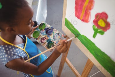 High angle view of elementary girl painting on canvas