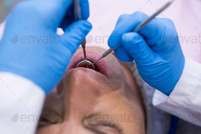 ]Doctor giving dental treatment to man at clinic