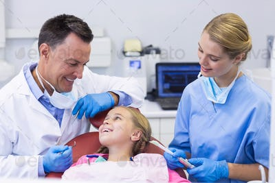 Dentist and nurse interacting with a young patient