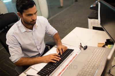 Businessman typing on keyboard at office dsek