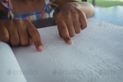 Cropped hands of girl reading braille