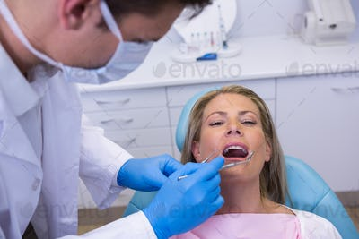 Doctor giving dental treatment to woman at clinic