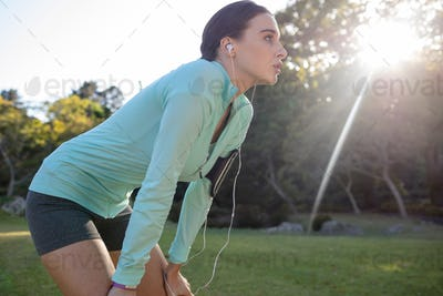 Exhausted female jogger listening to music and leaning on knees while exercising