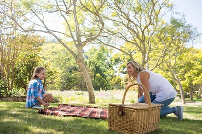 Mother and daughter spreading the picnic blanket