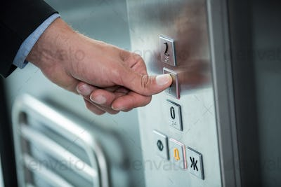 Hand of a businessman pressing the button in an elevator