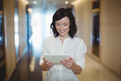 Female executive using digital tablet in corridor