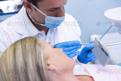 Dentist showing equipment to patient at medical clinic