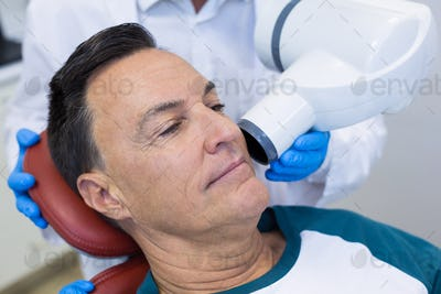 Mid section of dentist examining a male patient with dental tool