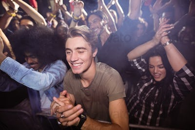 Young man amidst crowd enjoying at nightclub