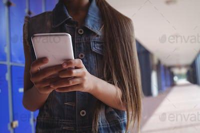 Elementary student using smartphone in corridor