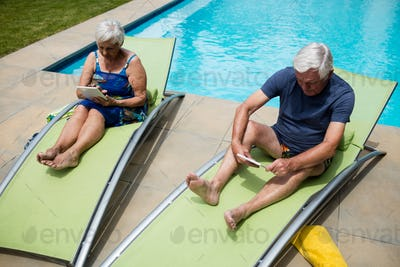 Senior couple using digital tablet on lounge chair