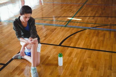 High angle view of woman using mobile phone in basketball court