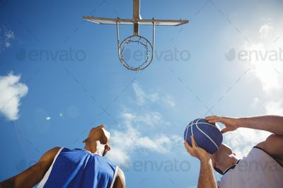 Low angle view basketball players practicing in court