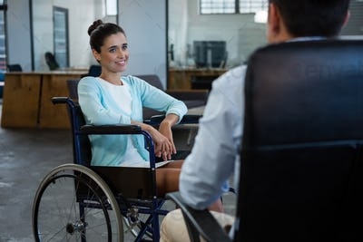 Businesswoman in wheelchair talking with colleague in office