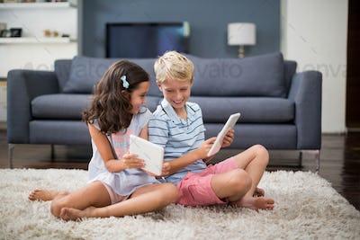 Siblings sitting on rug and using digital tablet in living room