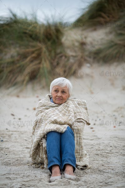 Senior woman wrapped in shawl on the beach