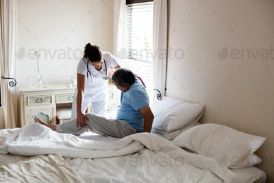 Female doctor assisting senior patient in bedroom
