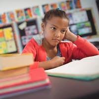 Thoughtful schoolgirl sitting at desk