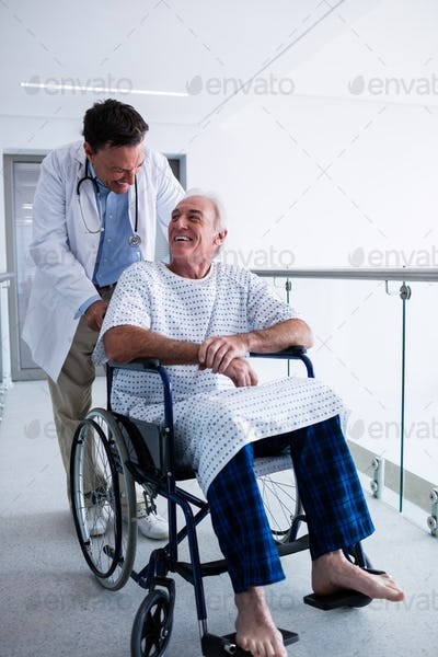 Doctor interacting with male senior patient on a wheelchair