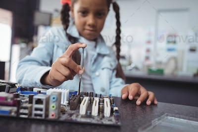 Elementary girl assembling circuit board at electronics lab