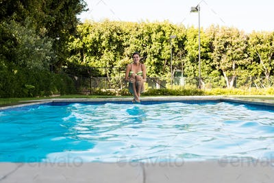 Young woman jumping in the pool