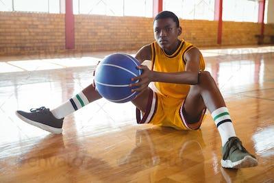 Portrait of teenage boy with ball sitting on floor