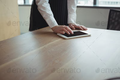 Mid section of businesswoman using digital tablet on desk