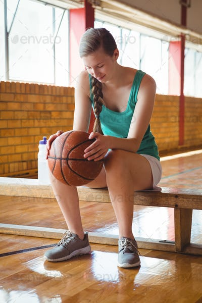 Smiling woman holding basketball while sitting on bench