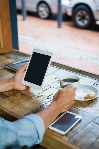 Person holding tablet computer by coffee cup at table