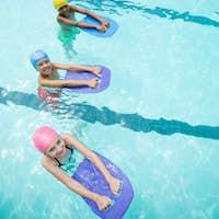 Children using kickboard while swimming in pool
