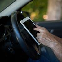 Senior man using digital tablet in car