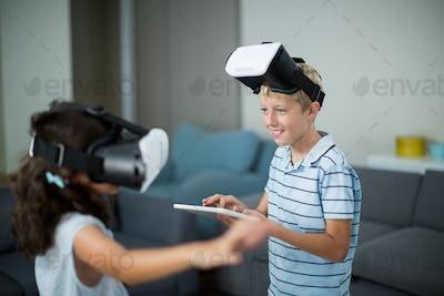Siblings using virtual reality headset and using digital tablet in living room