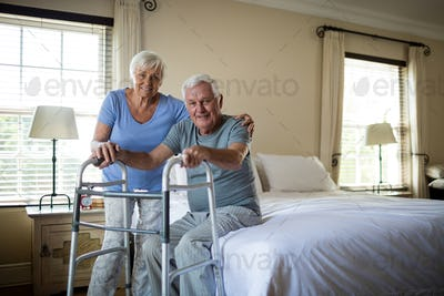 Senior woman helping man to walk with a walker