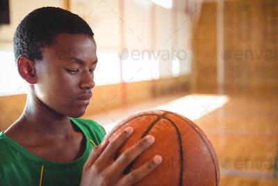Close up of teenage boy looking at basketball