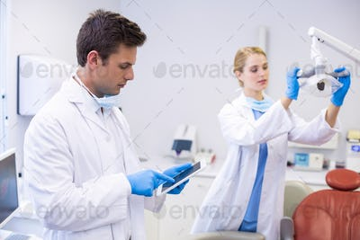 Dentist using digital tablet while his colleague adjusting dental light in background