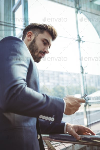 Attentive businessman using mobile phone