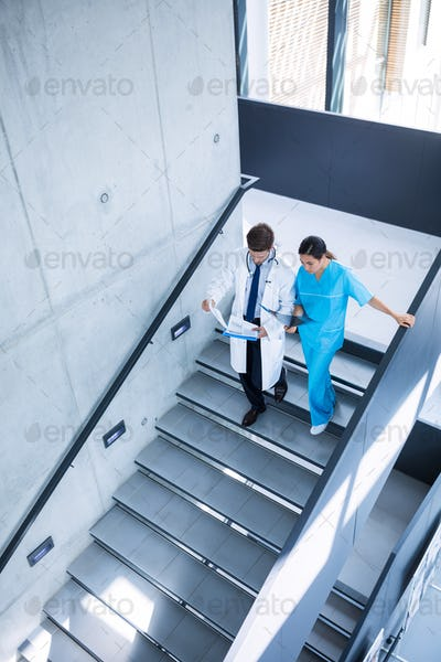Doctor and nurse discussing over a report while climbing down stairs