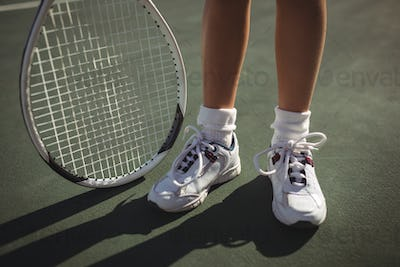Low section of girl with tennis racket