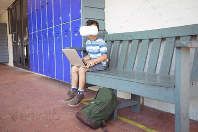 Full length of boy using laptop and virtual reality glasses while sitting on bench